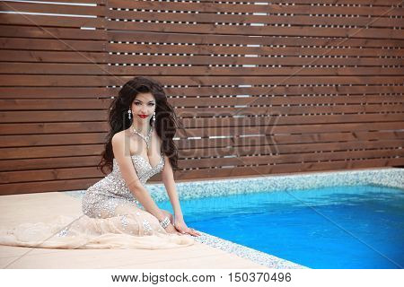 Attractive Young Smiling Brunette Woman In Elegant Dress Posing Near Blue Swimming Pool, Summer Vaca