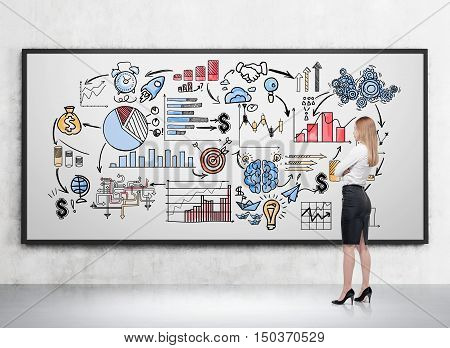 Side view of blond girl drawing icons on whiteboard in room with concrete walls and floor. Concept of business