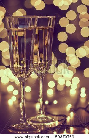 Two glasses of champagne with the bokeh background. Selective focus