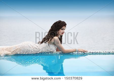 Glamour Gorgeous Woman Relaxing In Infinity Swimming Pool Looking At View. Luxury Life.