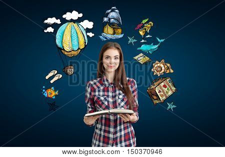 Smiling girl with large book standing against dark blue background and looking at the viewer. Travel sketches float around her.