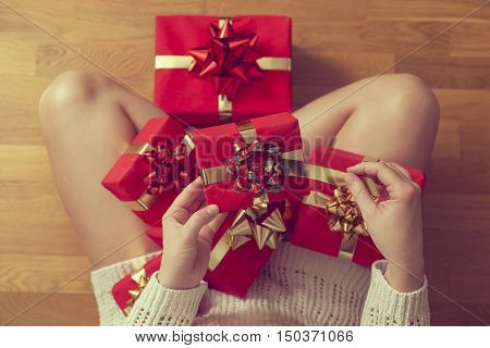 Detail of a woman sitting on the floor wearing a sweater and holding bunch of nicely wrapped presents in her lap