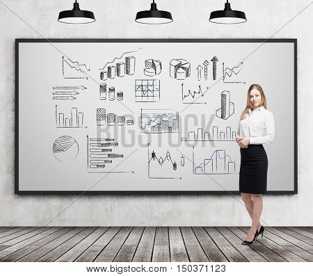 Smiling blond businesswoman standing near whiteboard with graphs on it. Concept of stats in business.