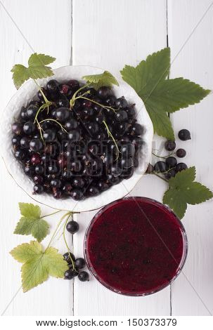 Gem of a black currant in a vase for a jam and currants in a white plate on a white wooden table. View from above.