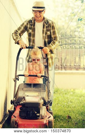 Little girl is helping her father to mow the lawn.