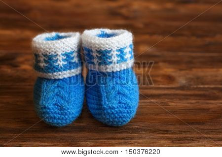 Blue hand made crochet baby booties on wooden background, copyspace, closeup