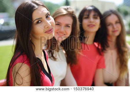 Four young cute women sit on bench outdoor at sunny summer day, focus on left woman