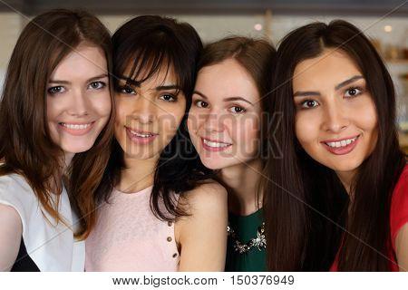 Four young beautiful women pose indoor, closeup, shallow dof