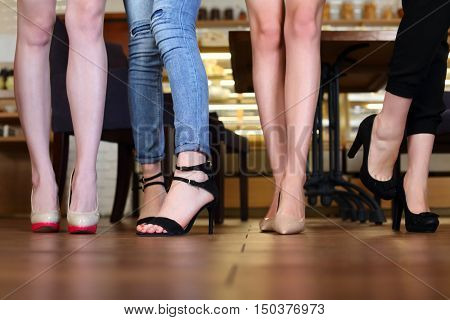 Legs in heels of four young women standing in cafe with wooden floor