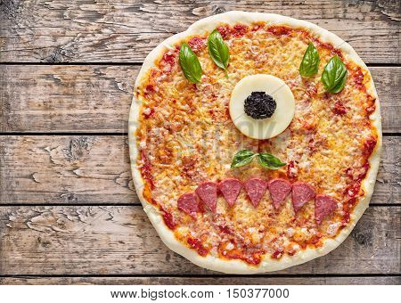 Halloween creative scary food eye cyclops monster zombie face pizza snack with mozzarella, basil and sausage on vintage wooden table background. Traditional holiday celebration party decoration recipe