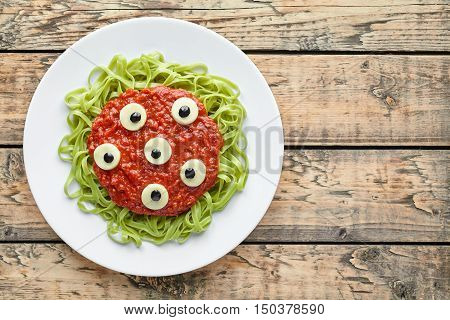 Spooky halloween monster green spaghetti pasta holiday decoration party food with fake blood tomato sauce and many mozzarella eyeballs on vintage wooden table background