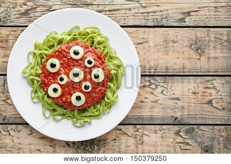 Scary halloween monster green spaghetti pasta holiday decoration party food with fake blood tomato sauce and many mozzarella eyeballs on vintage wooden table background