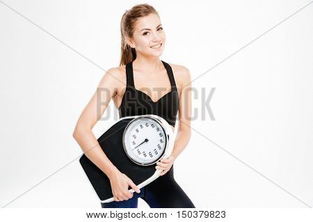 Happy fitness woman holding weighing machine isolated on a white background and looking at camera