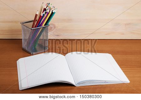 Exercise Book Into A Cell Lying On A Wooden Table.