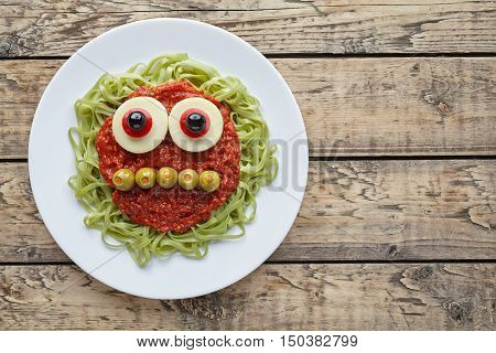 Green spaghetti pasta creative spooky halloween food monster with smile, fake blood tomato sauce and funny big mozzarella eyeballs holiday decoration kid party meal on vintage wooden table background.
