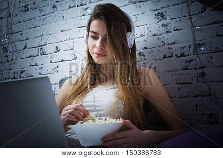 Teenage girl in bed with headphones, laptop and popcorn watching a movie at night. Pretty young woman enjoying movie or series on computer in her bedroom.