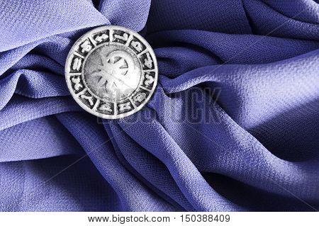 Silver zodiac brooch on purple crumpled silk as a background