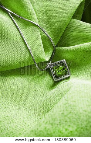Emerald pendant on a chain on green cloth as a background
