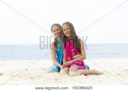 Lovely Mother And Girl Sitting On The Beach