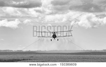 Spray plane swooping down and spraying chemical on a agriculture field at harvest in black and white