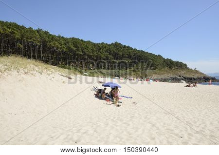 CANGAS DE MORRAZO, SPAIN - AUGUST 9, 2016: People in a summer day in Melide beach also known as Cabo Home Beach is located in a Natural space of Cangas de Morrazo in Pontevedra Galicia Spain.
