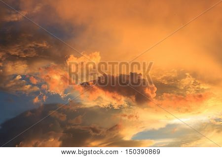 Fantastic red sunset and dark ominous clouds.Beautiful natural background and dramatic blue cloudy sunset sky