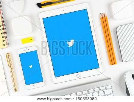 Moscow, Russia - October 04, 2016: Twitter application on display of iPad and iPhone. Twitter is popular social network service application