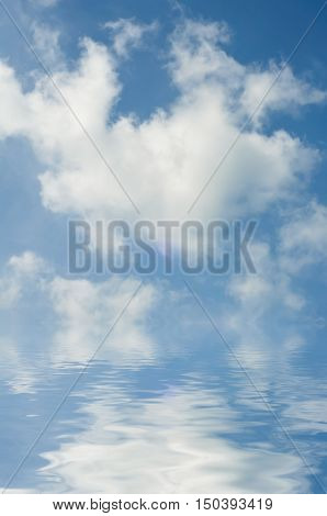 Fluffy white clouds in bright blue sky reflected in clear rippling sea or lake below horizon. The sky is photographed with water added artificially.