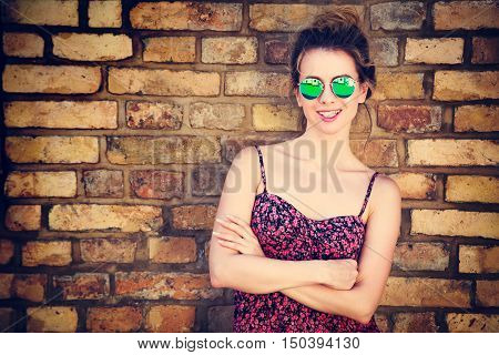 Portrait of Trendy Fashion Woman on Brick Wall Background. Girl in Summer Dress. Urban Street Style Concept. Toned Photo with Copy Space.