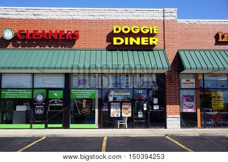 PLAINFIELD, ILLINOIS / UNITED STATES - SEPTEMBER 19, 2016: One may eat hot dogs and other fast foods at the Doggie Diner, and have one's clothes cleaned at the Perfect Fit Cleaners, in a Plainfield strip mall.