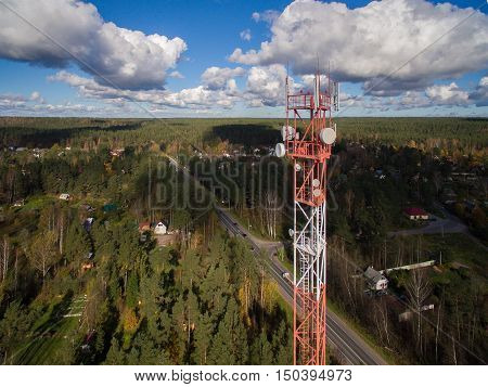 Aerial view of Antenna telecommunication tower multiple antenna and data transmitters. It is painted in white-red colors. She stand on a green meadow, and behind you can see the forest and road. Russia, 2106