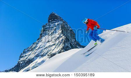 Man skiing in deep fresh powder snow with Matterhorn in background in Swiss Alps.