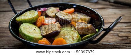 roasted vegetables on pot isolated on wooden table