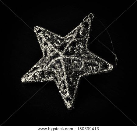 Golden artistic christmas star on the dark background. Christian holiday. Black and white photo. Symbolic object.