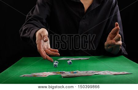 Man throwing dice on a gambling table with playing cards
