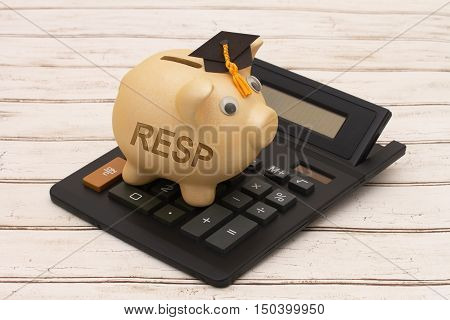 Educational Savings Plans A golden piggy bank with grad cap and calculator on a wood background with text RESP