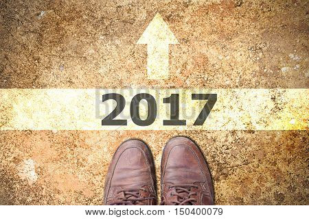 Male feet in old brown leather shoes stand on asphalt pavement with white arrows pedestrian crossing road marking start to 2017