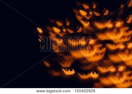 Halloween festive blurred background. Orange pumpkin faces on a black background.