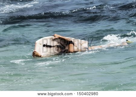Young Teen Girl With Board On Side In Ocean Waves Head Submersed In Water