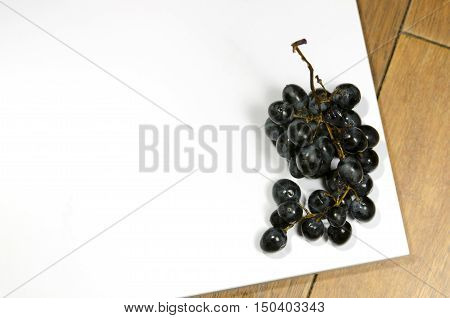 dark spoiled grapes on a white board