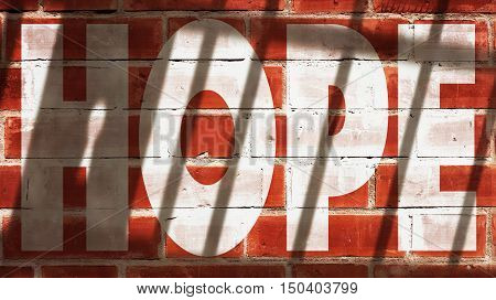 Hope Written On A Wall With Jail Bars Shadow