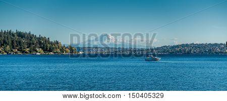 A view Mount Rainier and a boat on Lake Washington. Photo taken at Seward Park near Seattle.