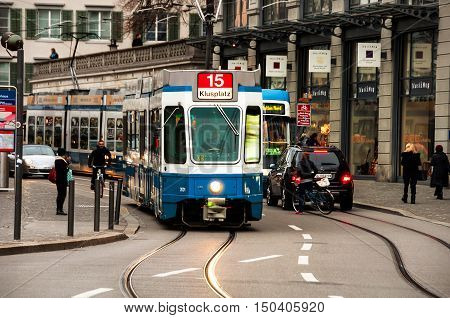 ZURICH SWITZERLAND - FEBRUARY 27 2014: Blue Tram in the city center with local people. The system was electrified in 1890s and was developing since intro a huge network
