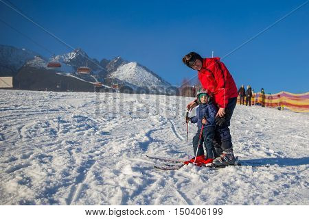 Happy little boy learning skiing with his father during winter holidays in High Tatras, Slovakia