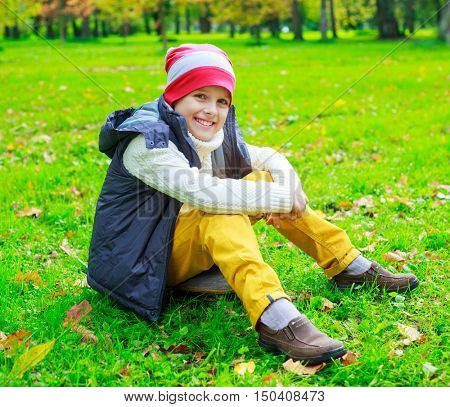 happy ten years old boy in the autumn park  sitting on the grass