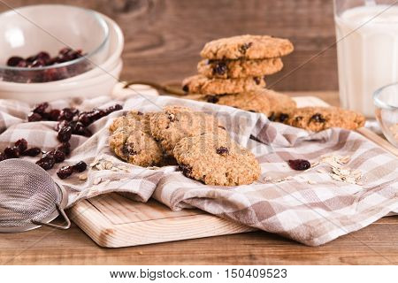 Stack of oatmeal cookies on wooden breadboard.