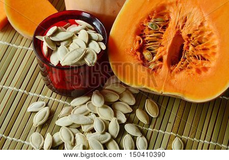 dried pumpkin seeds are snacks that are healthy. dried pumpkin seeds with fresh pumpkin on Bamboo mat background