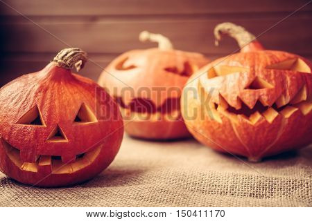 Autumn background with orange halloween pumpkins on rustic fabric