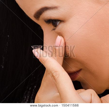 Beauty, vision, eyesight, ophthalmology and people concepts. Young Korean woman putting on contact lenses isolated on black background.