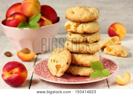 Biscuits with apricots and fresh apricots in a pink bowl on a white background